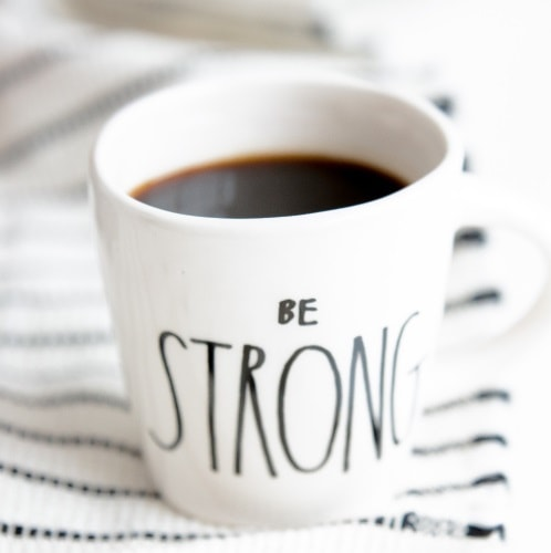 A cup of black coffee with 'Be Strong' written on it